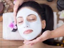 Spa terapi för den unga kvinnan som har den ansikts- maskeringen på skönhetsalongen Royaltyfri Bild
