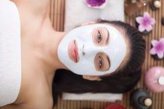 Spa terapi för den unga kvinnan som har den ansikts- maskeringen på skönhetsalongen Arkivfoton