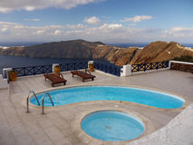 Spa terrace, Santorini. Spa terrace with turquoise-colored pools and sun loungers. Fantastic panoramic view of the Aegean sea level with volcanic islands stock images