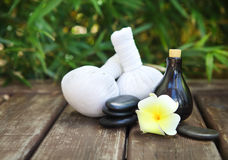Spa theme objects with frangipani flower. Compress balls, stacked basalt stones and bamboo background Stock Images