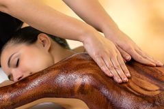 Spa therapist applying curative hot chocolate on woman royalty free stock photography
