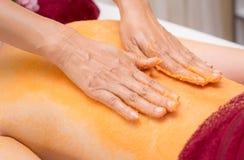 Spa Therapist is applying orange scrub salt on to woman back. Spa Therapist is applying orange scrub salt on to a woman back Stock Images