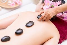 Spa therapist Placing Black hot stone on to a woman back. Spa therapist is Placing Black hot stone on to a woman back Stock Photography