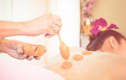 Spa Therapist is putting Orange salt scrub on to women back Stock Image