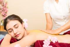 Spa Therapist rubbing Scrub on to women back. Spa Therapist is rubbing Scrub on to women back royalty free stock image