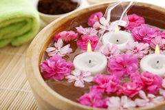 Spa therapy, flowers in water, on a bamboo mat. Royalty Free Stock Photography