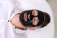 Spa therapy for men receiving facial black mask. Cleaning the face of a man in a beauty salon. Spa therapy for man receiving facial black mask stock photo