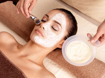Spa therapy for woman receiving facial mask. Spa therapy for young woman receiving facial mask at beauty salon - indoors stock photo