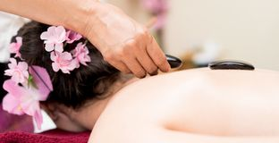 Spa Therpist placing black hot stone onto a woman back Royalty Free Stock Images