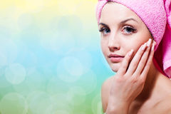 Spa time: blue eyes sexy girl in towel touching her face silk skin & looking at camera on light copy space background, closeup po. Blue eyes sexy young lady Royalty Free Stock Photo