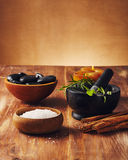 Spa tools. Bath salt, mortar with herbs, a bowl with hot stones and candles, some cinnamon sticks on the table Royalty Free Stock Photography