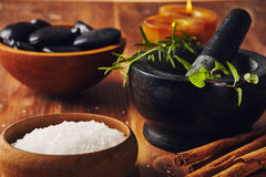 Spa tools. Bath salt, mortar with herbs, a bowl with hot stones and candles, some cinnamon sticks on the table Stock Photo
