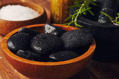 Spa tools. Bath salt, mortar with herbs, a bowl with hot stones and candles, some cinnamon sticks on the table Royalty Free Stock Image