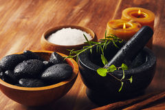 Spa tools. Bath salt, mortar with herbs, a bowl with hot stones and candles, some cinnamon sticks on the table Royalty Free Stock Photos