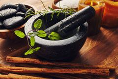 Spa tools. Bath salt, mortar with herbs, a bowl with hot stones and candles, some cinnamon sticks on the table Stock Image