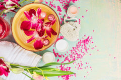 Spa tools for body care, flowers and water bowl on light wooden background, top view, border. Stock Photos