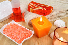 Spa tools in orange. Spa therapy in energetic orange colors. Burning candles royalty free stock images