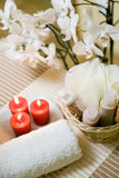 Spa towel and candles. A spa composition with three red candles and white towel, with an orchid as background Stock Images