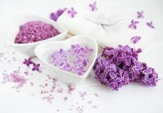 Spa towel and massage products with lilac flowers. On a white wooden background royalty free stock photo