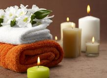 Spa towels candles and flowers. A view of soft, fluffy spa towels with flowers and several lighted candles in a relaxing setting Stock Images