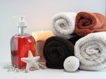Spa towels with soaps and lit candle Stock Photos