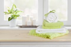 Spa towels on wooden table over blurred salon window background.  stock images