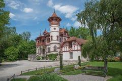 Spa trädgård som herrsching med den härliga slotten Arkivbild