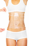 Spa treatment. A picture of a sexy female body being wrapped around with foil to reduce fat over white background Royalty Free Stock Image
