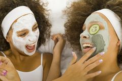 Spa treatment. Happy young women lying on towel putting puryfing mask Royalty Free Stock Photography