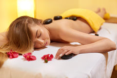 Spa Treatment. Beautiful Blonde Gets Stone Massage.  Wellness Co Royalty Free Stock Photography
