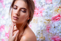 Spa treatment. Beautiful sensual woman posing on a background of roses. Inspiration of spring and summer. Perfume, cosmetics concept