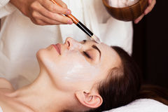 Spa treatment. Beautiful woman with facial mask at beauty salon.