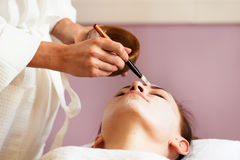 Spa treatment. Beautiful woman with facial mask at beauty salon. royalty free stock images