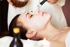 Spa treatment. Beautiful woman with facial mask at beauty salon. Royalty Free Stock Photos