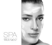 Spa Treatment and Beauty Concept. Template Design. Spa treatment and beauty concept. Portrait of a gorgeous woman with cosmetic cream on her cheeks and forehead royalty free stock photos