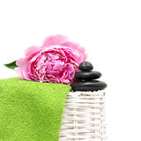 Spa treatment. Black stone, green towel, flower Royalty Free Stock Images