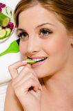 Spa treatment by eating cucumber: young sensual beautiful veggie girl attractive woman with blue eyes holding green cucumber. Between white teeth happy smiling Royalty Free Stock Image