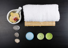 Spa treatment essentials. Beauty and spa treatment essentials on a dark wooden background Royalty Free Stock Photo