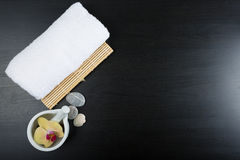 Spa treatment essentials. Beauty and spa treatment essentials on a dark wooden background Royalty Free Stock Photography
