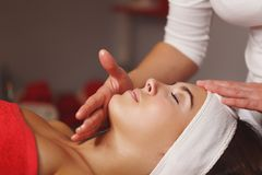 Spa treatment. Face massage. Massage the forehead and chin area client close-up. Moistening with oil. Restorative procedures Royalty Free Stock Image