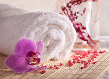 Spa Treatment. Fluffy towel, an orchid and bath salt on bamboo background Stock Photography