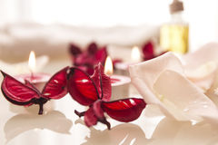 Spa treatment: ready for relax. Spa treatment preparation for relax with aroma candles and rose petals Royalty Free Stock Images