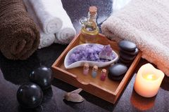 A spa treatment set with purple salt, hot aromatic oil and soft towels. Black Bian stones for massage lie next to the Stock Photos