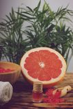 Spa treatment set with red bath salt, massage oil and towel next to red grapefruit and palm.  stock photography
