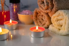 Spa treatment set with scented salt, candles, towels and aroma oil stock photo