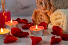 Spa treatment set with scented oil, candles, rose petals and flowers royalty free stock photography