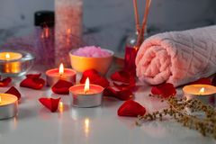 Spa treatment set with scented oil, salt, candles, rose petals and flowers royalty free stock image