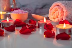 Spa treatment set with scented oil, salt, candles, rose petals and flowers royalty free stock photos