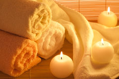 Spa Treatment. Spa towels and candle on bamboo background Royalty Free Stock Photography