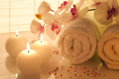 Spa Treatment. Spa towels, candle and orchid on bamboo background Royalty Free Stock Image